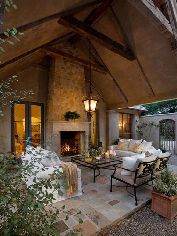 Stone and wood, lanterns and candles, potted greenery, comfy seating arrangements…Elegant, sophisticated space.
